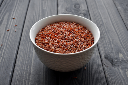 Red rice in a ceramic bowl against dark rustic wooden background