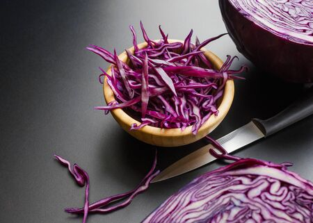 chopped red cabbage salad in wooden bowl with a half of cabbage head and the knife over dark gray background