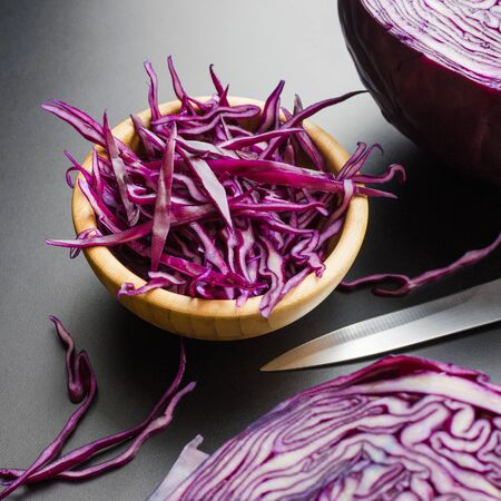 chopped red cabbage salad in wooden bowl with a half of cabbage head and knife, dark gray background