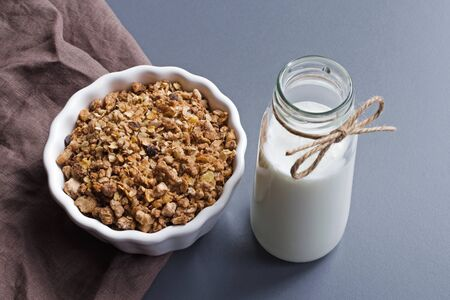 greek yoghurt drink and muesli breakfast over gray table background with linen napkin