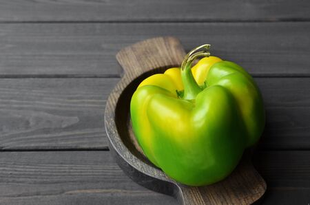 Organic fresh green bell pepper in wooden plate on dark rustic wooden background, top view, copy space, healthy food concept