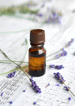 Olio a base di erbe biologico in bottiglia di vetro scuro e fiori di lavanda freschi su sfondo chiaro di tavolo in legno vecchio Archivio Fotografico