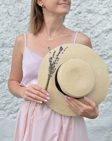 Beautiful straw hat with black ribbon and dry organic lavender flowers bouquet in female hands