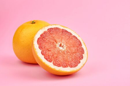 Fresh whole and cut red grapefruit citrus fruits on pink background, copy space