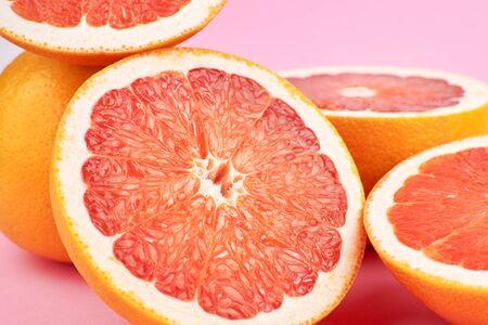 Grapefruit citrus fruits closeup on pink background.