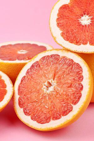 Heap of fresh cut grapefruit citrus fruits on trendy pink paper background