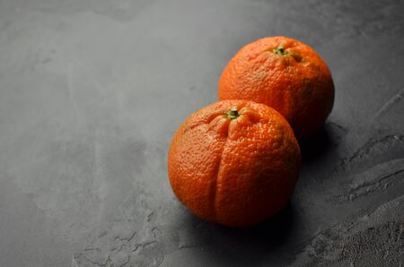 Fresh mandarin citrus fruits on black grunge background. Two whole tangerines. Copy space.