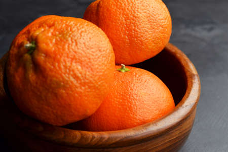 Big whole orange mandarins on black grunge background. Darkmood food pfotography.