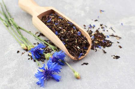 Black tea with flower petals of cornflower and thyme herb in wooden scoop, fresh blue cornflowers. Reklamní fotografie