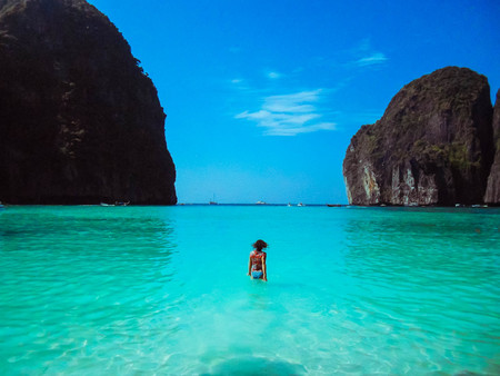 The transparent, turquoise sea on both sides of rocks with green vegetation. The girl enters the water, the view from the back. On a Sunny summer day. On the horizon small boats. The bright blue sky.