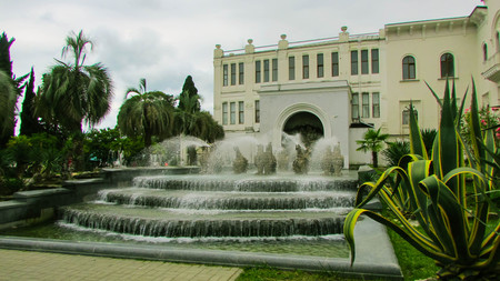 sukhumi: Flowing speed of the fountain in the square in front of the white building. Around the green palm trees. In the foreground a large agave. The area in front of the fountain are paved. Summer day. Cloudy.