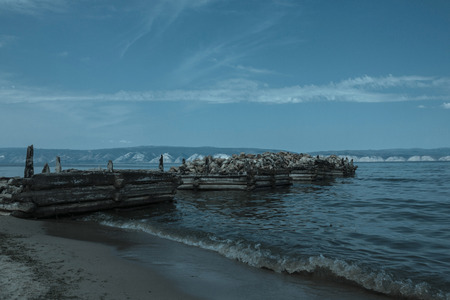 The foundation of the old pier of logs and stones. The flooring is destroyed. Small waves with foam. On the far side of the mountain. Sky clouds. Retro. Stock Photo