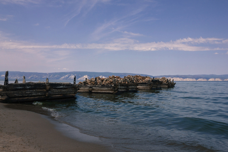 The old, abandoned pier goes into the sea. Small waves, sandy shore. In the distance, white mountains, hills. Blue water. Bright sky, clouds. Day. Theres no one.