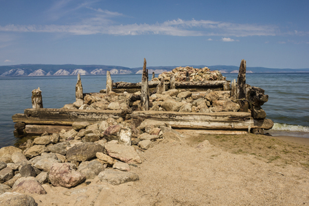 uncouth: The ruined old pier goes into the distance. In the foreground are stones, logs, sand. Nobody here. On the opposite shore white mountains. Sunny day. Blue sky, small clouds.