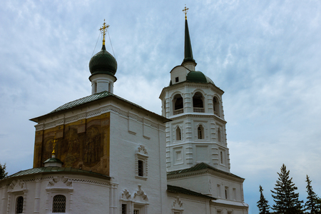 rood: White orthodox temple on a background of a cloudy sky. Dome of the church with a cross. Bell tower. Near several oil.