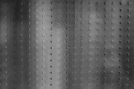 Matgegolfd glas, waarachter zwart-wit, wazig, verticaal, onduidelijke contouren. Textuur, glanzend oppervlak. Stockfoto