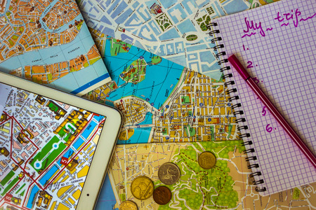 Maps of Stockholm, Venice, Florence, France. On the tablet is a map of Paris. Small coins of European countries. Notepad with the inscription My trip. View from above. Stock Photo