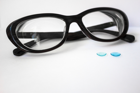 On a white background glasses with a black rim and two hard contact lenses. Modern correction of vision.
