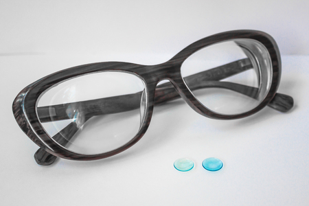 Two small lenses for the eyes and thick female glasses. Myopia of a high degree. Modern correction of vision. Rigid contact lenses are blue. White background.