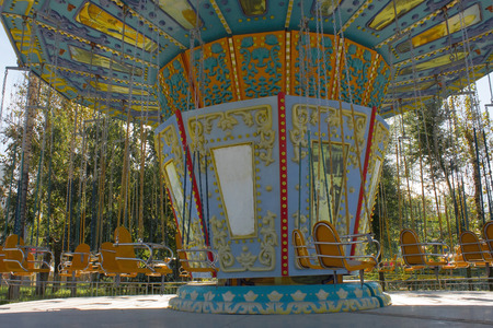 Painted old childrens merry-go-round in the park. All the chairs are free, there is no one. Sunny day. Yellow and green trees in the background.
