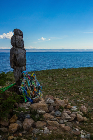 An ancient idol, carved from a tree, stands on the shore of a lake. Bright blue water, clear sky, green grass. Skyline. At the feet of the figure are colored ribbons. Subject of worship, ancient religion.