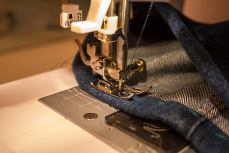 Close-up of a sewing needle stuck in a denim fabric. Straight stitch. Sewing at home. Upper lighting, evening.