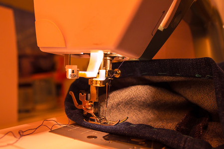 Electric sewing machine. There is a cloth under the needle. Muted lighting, evening.