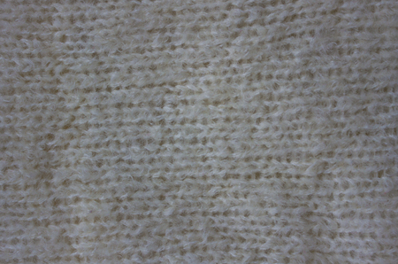 Knitted texture of white color. Knitwear made of natural wool. Warm, cozy, winter thing.