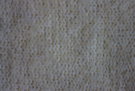 Single-knitting knitting from natural white wool. Fluffy, nap structure, vertical rows of the wrong loops. Warm, winter clothes.