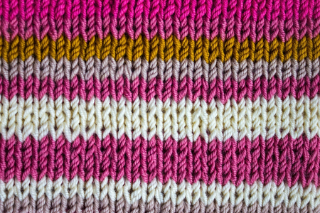 Home knitting, needlework from natural wool. Drawing in the strip. Face hinges. Colorful, bright background. Stock Photo
