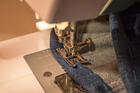 Modern electric sewing machine. The needle is stuck into the denim fabric. Warm lighting, evening.