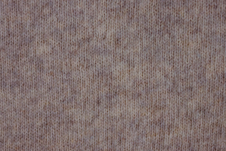 Knitted fabric made of natural wool. Beige shade without pattern. A small pile, mohair thread. Warm winter clothes made of natural materials.