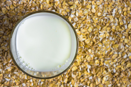On a yellow background, a glass of milk is standing out of the cereal. Daylight, the background is blurred. View from above.