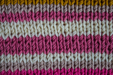 Knitted fabric handmade. Color strips of different widths. Pink, gray, white and brown. Large manual knitting. Stock Photo