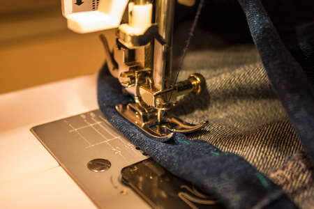 A line on the sewing machine. The needle is inserted into the product. A modern household sewing machine. Tailoring craft. Stock Photo