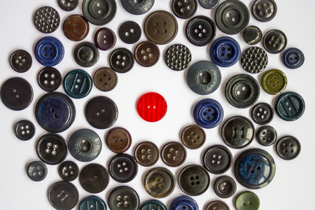 soltería: A bright red button for clothes among other black, dark buttons. Confrontation, loneliness, violation of rules and dress code. White background, top view.