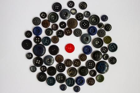 De rode knop is omringd door andere knoppen met een donkere kleur. Onderscheid, individualiteit, heldere persoonlijkheid tussen de grijze wereld. Afwijzing, isolatie, afwijzing door anderen. Protesteer tegen gewoon, grijs.