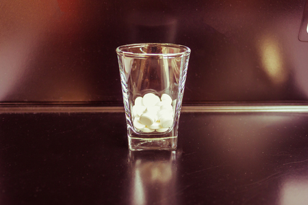 On the bar, there is a glass with tablets. The background is blurred. Drug for drinking, alcohol dependence. Treatment of the consequences of drunkenness. Stock Photo