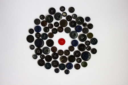 soltería: One red button among the mass of black. Enemy, scout, insider. Difference from the others, individuality, opposition. Dark circle of buttons, light background, top view. Foto de archivo