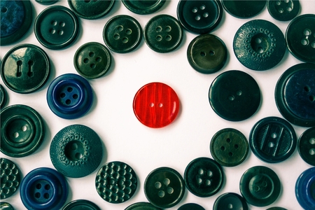 soltería: Around the red button is a background of dark buttons of different sizes. Confrontation of the individual and the hostile world. Loneliness among people. Difference from the others. Foto de archivo