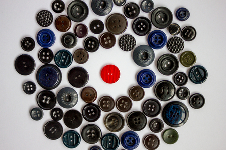 soltería: In the mass of dark buttons for clothing one red. Hostile environment, gray, boring, ordinary world. Misunderstanding of others, loneliness, protest against everyday life.