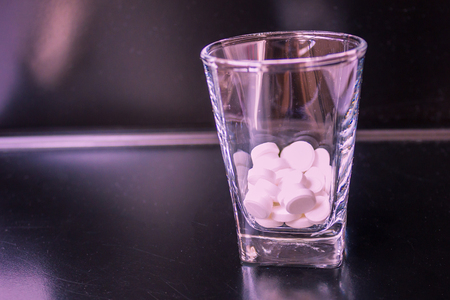 White tablets in a vodka glass. A shiny black bar, the background is blurred. Violet tinting. Stock Photo