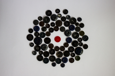 In the middle of the circle of different black buttons there is one red button. Difference from others, a bright personality among the gray world. Isolation, hostile environment, confrontation. White background, daylight.