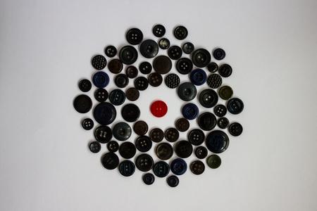 In het midden van de cirkel van verschillende zwarte knoppen is er een rode knop. Verschil van anderen, een heldere persoonlijkheid tussen de grijze wereld. Isolatie, vijandige omgeving, confrontatie. Witte achtergrond, daglicht. Stockfoto - 88335926