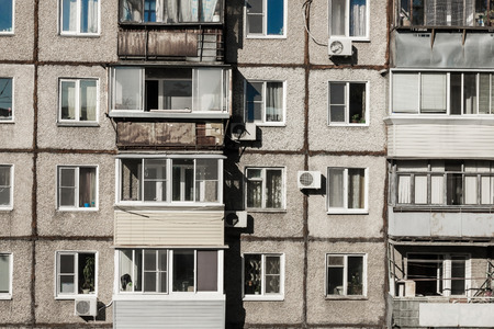 The wall of a dilapidated apartment building, windows and old balconies. A terrible condition of housing, bad conditions, cheap apartments. Stok Fotoğraf