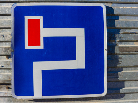 Road sign on a blue background. The confused path leads to a dead end. A desperate situation, a false direction. Solar lighting.