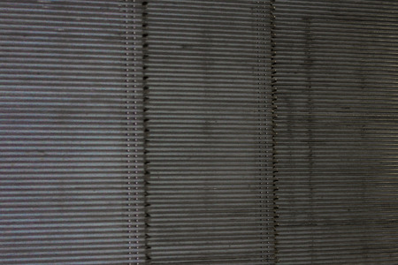 Ribbed texture of cold metal. Silver, gray color. Wide vertical stripes. Side lighting. Banco de Imagens