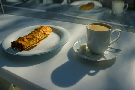 On a white table near the window a cup of coffee and a plate with baking. White dishes are reflected in the glass. Solar lighting from the street, top view. City cafe.