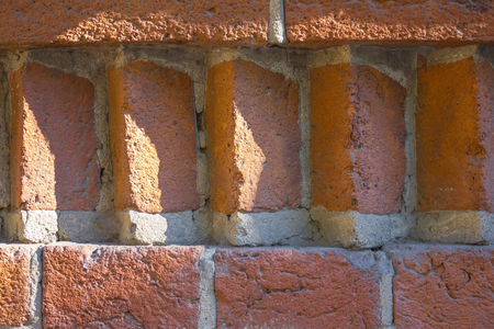 eldest: Figured element of an orange brick wall. Between the horizontal rows of bricks are located vertically and diagonally. The stitches are sealed with gray cement. Solar side lighting. Stock Photo