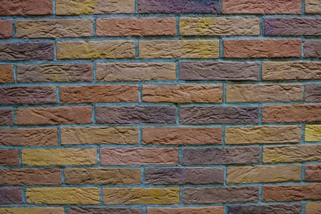 The wall is lined with brown, yellow, orange and purple bricks. Gray seams.